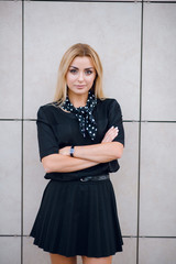 Close up portrait of pretty young woman with blonde hair in stylish black dress standing against grey wall. Urban background.