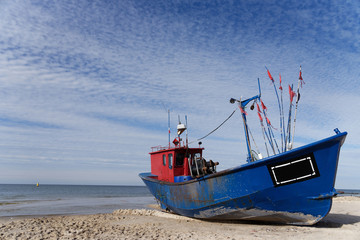 A blue fishing boat standing on the sandy shore of the sea.