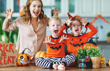 happy Halloween! family mother and children getting ready for holiday cutting pumpkin