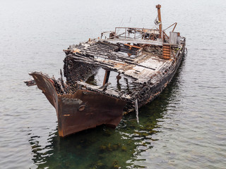 Rotting, abandoned ship on a water of sea, a symbol of decadence and degradation
