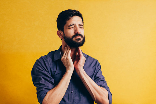 Young man having sore throat and touching his neck over yellow background. Hard to swallow