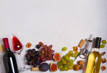 Glass and bottle of wine with grapes, figs and nuts on white stone texture background. View from above, top studio shot