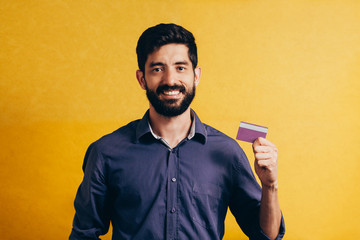 Portrait of a smiling bearded man showing credit card isolated over yellow background