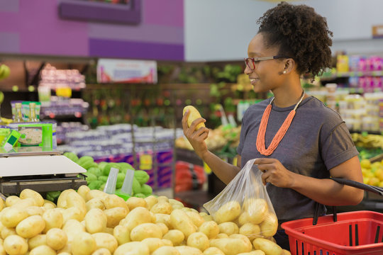 Woman holding potato and shopping in department store