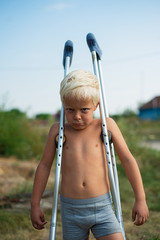 Boy man without a shirt standing on crutches outdoors