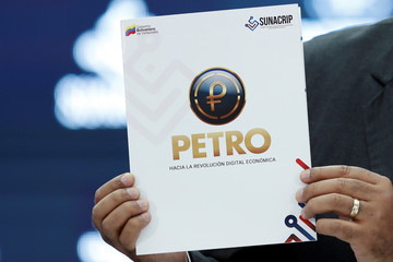 Venezuela's President Nicolas Maduro shows a document as he speaks during the kick-off event for the international trading of Petro, the cryptocurrency developed by the Venezuelan government, in Caracas