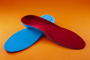 Foot support and healthy feet concept with orthopedic shoe insoles isolated on orange background