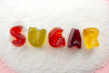 sweet food, unhealthy diet and refined sugars concept with close up on the word sugar written into a pile of white granulated sugar with gummy letters