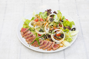 Close up of rare seared tuna slices with fresh vegetable salad on a plate with wood background