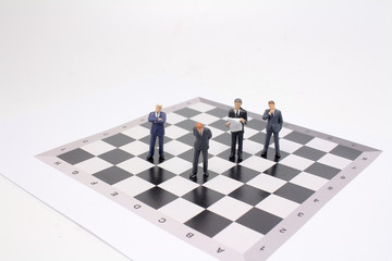 a business men figures stand on chess board