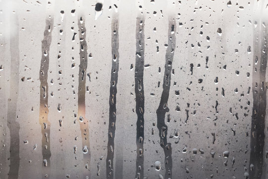 Wet, steamy glass windows with gray steam and water droplets as background