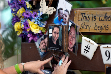Sharon Mackrell adds photos of her friend Cameron Robinson, one of the 58 victims of the October 1, 2017 mass shooting, at the Las Vegas Healing Garden during the one-year anniversary of the shooting in Las Vegas
