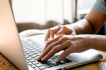 Closeup image of hands working and typing on laptop keyboard in front of the window in soft light