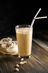 Iced coffee in tall glasses with milk and straws on board over rustic wooden table, white wall and jug at background, copy space. Summer refreshing beverage ice coffee drink concept