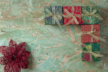 Gifts with a red ribbon on a wooden surface copy space. Gifts in wrapping paper with space for text.