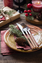 Christmas Setting Table. Dinner plate, silverware, fir tree, gift boxe, candle and festive decoration. Holiday Food Concept