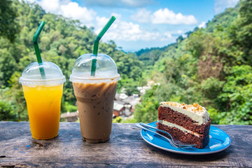 Cake and coffee on a table with a view of the mountains and green forests.