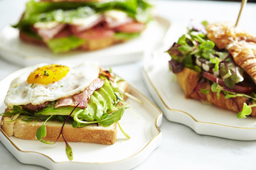 Bacon and avocado toast with croissant sandwich