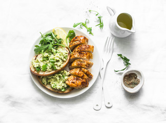 Baked chicken breast and avocado toast-healthy lunch on a light background, top view