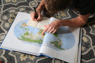 Man makes a list of places to visit world wide.