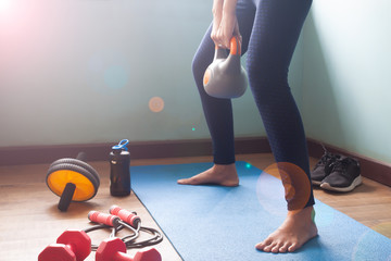 Woman exercise with kettlebell at home
