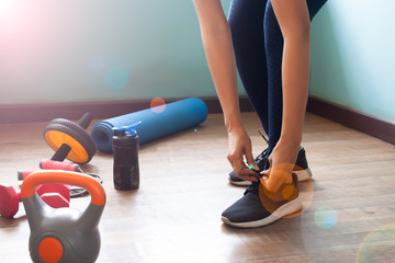 Sporty woman workout at home, Focus on tying shoes