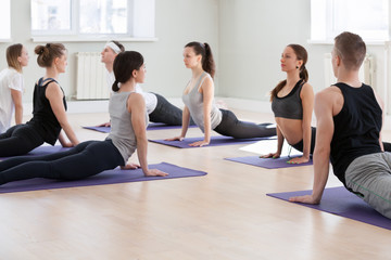 Group of young sporty people practicing yoga lesson, doing upward facing dog exercise, Urdhva mukha shvanasana pose, working out, indoor full length, students training in sport club, studio