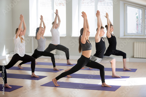 Group Of Young Sporty People Practicing Yoga Lesson Doing Warrior