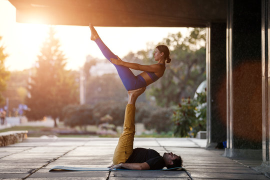 Young man and woman practicing acro yoga on street