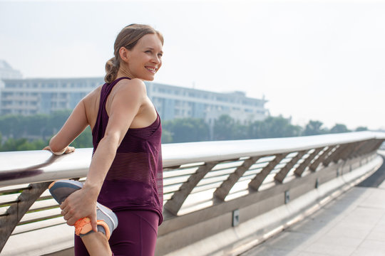 Portrait of happy female athlete stretching leg on bridge. Caucasian woman warming up before jogging outdoors. Fitness concept