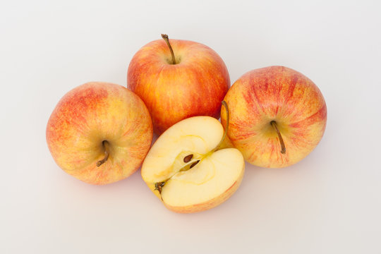 Red and yellow apples on white background. One cut in half. Isolated.