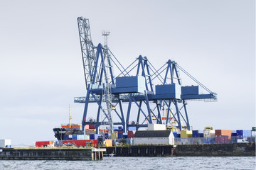 Container terminal crane gantry for loading and offloading cargo freight shipping at quay yard harbour dock on sea coast Greenock Scotland UK