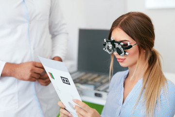 Eye Exam. Woman In Optometry Glasses Reading Eye Test Card