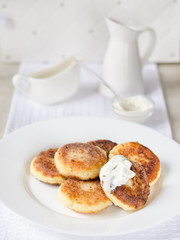 Cheese pancakes, curd cheese pancakes in cast iron frying pan on white background