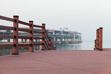 Empty red wooden pier in foggy evening