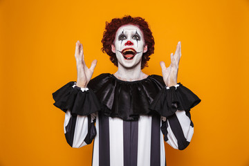 Happy clown looking and raise hands up to copy space