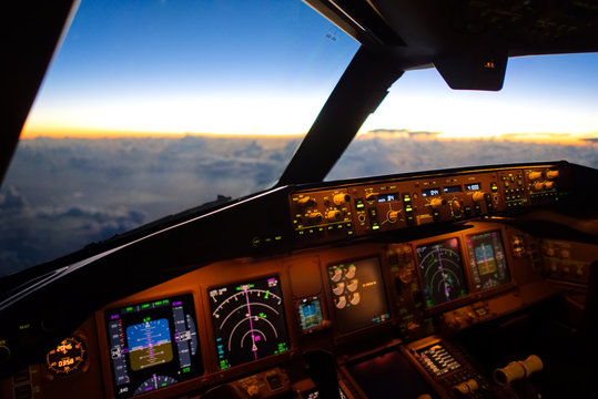 The view from commercial airplane, seen from captain seat in cockpit in the morning twilight during flying above the cloud over the ocean. Modern aviation concept.