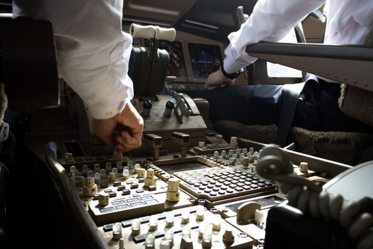 Both pilots working on the airplane. Seen from their back inside cockpit while captain is tuning radio knob to communicate with Air traffic controller (ATC). Modern aviation concept.