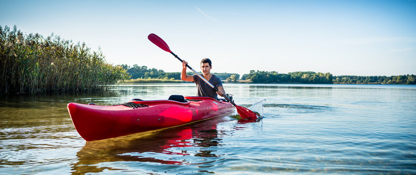 Portrait of man kayaking on idyllic lake using paddle
