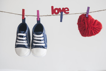 Baby shoes and photo hanging on the clothesline