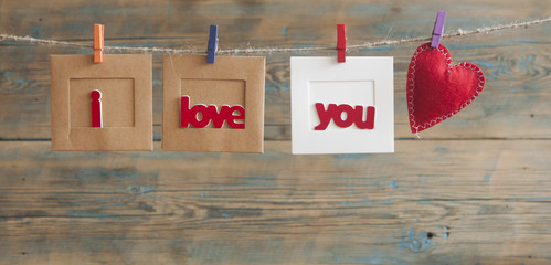Paper photo frame with written message spelling I love you and red hearts hanging on rope