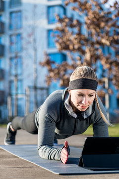 High-angle view of a fit young woman watching a motivational video on tablet PC, while exercising the forearm plank position on a mat outdoors in the park