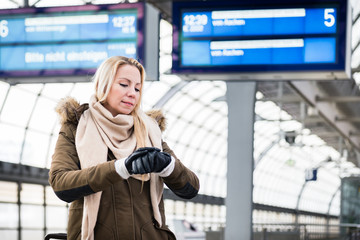 Woman looking at wristwatch in train station as her train has a delay, she is impassionate and late