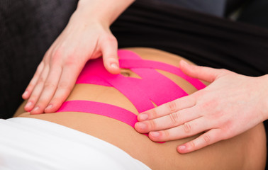 Physiotherapist doing alternative kinesio tape therapy on woman's abdomen