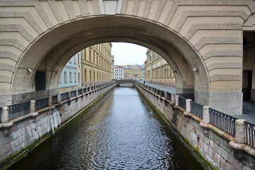Water channel under the arch of whose banks are lined with old granite fence. St. Petersburg, Russia, Europe