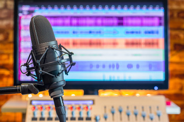 condenser microphone on screen and digital sound mixer background. recording, broadcasting concept
