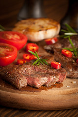 Canvas Prints grilled fillet steak with tomatoes and roast vegetables on an old wooden board, background.