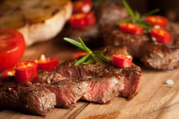 Canvas Prints Meat grilled fillet steak with tomatoes and roast vegetables on an old wooden board, background.