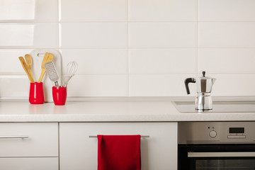 Interior white kitchen with kitchen tools and red crockery.