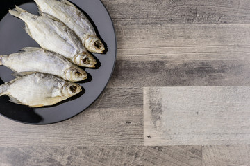 beer snack: 4 sun-dried freshwater salt fish on black plate - a source of vitamins and protein, grey table, free space